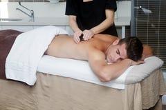 Knappe mens die massage met hete stenen krijgen Stock Afbeeldingen