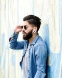 Knappe mens die met baard aan muziek met oortelefoons luisteren stock foto's