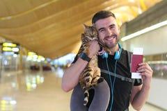 Knappe mens die met zijn kat reizen stock foto