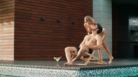 Knappe mens die mobiele telefoon met behulp van dichtbij pool bij luxehuis stock video