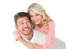 Knappe mens die op de rug aan zijn meisje geven Stock Foto's