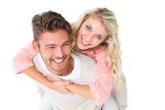 Knappe mens die op de rug aan zijn meisje geven Stock Afbeelding