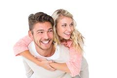 Knappe mens die op de rug aan zijn meisje geven Stock Foto