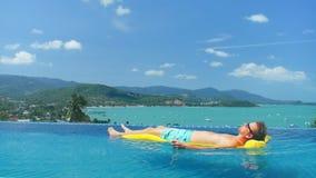 Knappe mens die op gele matras in de pool van de wateroneindigheid in luxevilla drijven stock video