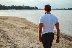 Knappe mens die op het strand loopt Stock Fotografie