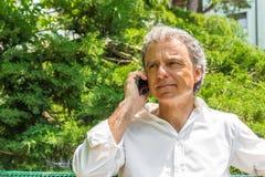 Knappe mens die op middelbare leeftijd op mobiele telefoon spreken Stock Foto