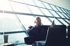 Knappe mens die op mobiel in een elegant bureau spreken Stock Foto