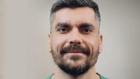 Knappe mens die oprecht uitdrukkend zijn tevreden staat, close-upemoties glimlachen stock footage