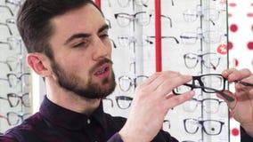 Knappe mens die paar glazen onderzoeken bij de optometristenopslag stock video