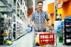 Knappe mens die in supermarkt winkelen stock afbeeldingen