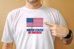 Knappe mens die trots wit overhemd met de vlag van de V.S. dragen stock foto