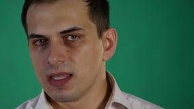 Knappe mens die verschillende emoties tonen Sluit omhoog Groene Achtergrond stock video