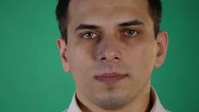 Knappe mens die verschillende emoties tonen Sluit omhoog Groene Achtergrond stock footage
