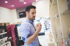 Knappe mens die voor fragrances winkelen stock afbeelding