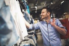 Knappe mens die voor kleren in opslag winkelen stock foto's