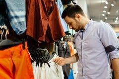Knappe mens die voor kleren winkelen stock foto's