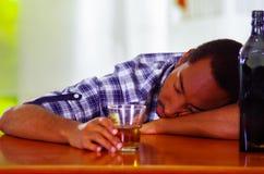 Knappe mens die witte blauwe overhemdszitting dragen door bar tegen over bureau gedronken slaap, alcoholisch concept te liggen stock foto's