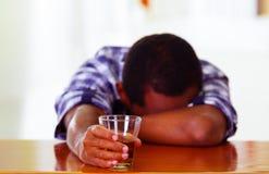 Knappe mens die witte blauwe overhemdszitting dragen door bar tegen over bureau gedronken slaap, alcoholisch concept te liggen stock foto