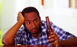 Knappe mens die witte blauwe overhemdszitting dragen door bar tegen over bureau te liggen die bruine bierfles, gedronken gedeprim stock afbeeldingen
