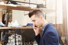Knappe mens die zich buiten opslagvenster bevinden op telefoongesprek royalty-vrije stock afbeeldingen