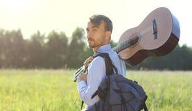 Knappe mens die zich op het de zomergebied bevinden met akoestische gitaar a Royalty-vrije Stock Foto