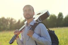 Knappe mens die zich op het de zomergebied bevinden met akoestische gitaar a Stock Foto