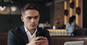Knappe mens gebruikend smartphonezitting in koffie of coworking bureau Portret van succesvolle Zakenmanondernemer stock videobeelden