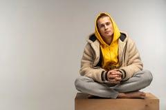 Knappe mens in gele hoodiezitting op houten kubus stock afbeeldingen