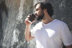Knappe mens het besteden tijd met drank in openlucht stock afbeelding