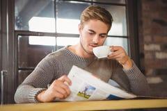 Knappe mens het drinken koffie en het lezen van krant stock afbeeldingen