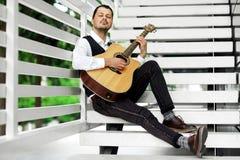 Knappe mens het spelen gitaar op de treden Ernstig mannetje die in openlucht ontspannen Stock Foto's