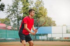 Knappe mens in het tennisracket van de overhemdsholding en kijken geconcentreerd terwijl status op tennisbaan Royalty-vrije Stock Afbeelding