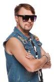 Knappe mens in jeansvest en zonnebril die, maniermens stellen Over wit stock afbeelding