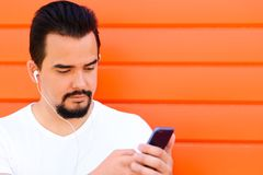 Knappe mens met baard en snor die aan muziek luisteren of op iets op het scherm van zijn smartphone met oortelefoons letten royalty-vrije stock afbeelding