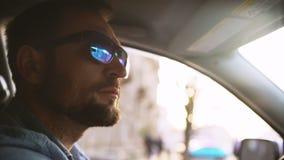 Knappe mens met baard in spiegelzonnebril die auto in stad met sunflare drijven stock videobeelden