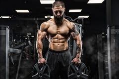 Knappe mens met grote spieren, die bij de camera in de gymnastiek stellen stock foto's