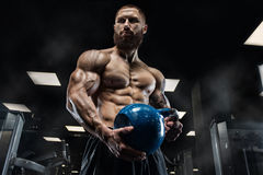 Knappe mens met grote spieren, die bij de camera in de gymnastiek stellen stock afbeeldingen