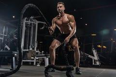 Knappe mens met grote spieren, die bij de camera in de gymnastiek stellen stock afbeelding