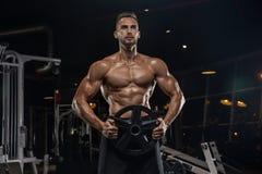 Knappe mens met grote spieren, die bij de camera in de gymnastiek stellen royalty-vrije stock afbeeldingen