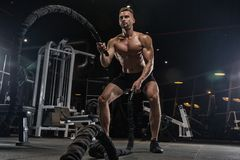 Knappe mens met grote spieren, die bij de camera in de gymnastiek stellen royalty-vrije stock afbeelding