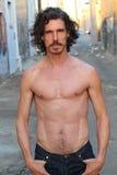 Knappe mens met lange haar en baard Hij stelt voor camera enkel met open jeans en toont zijn spieren Abdominals Stock Foto