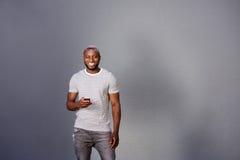 Knappe mens met slimme telefoon die zich door grijze muur bevinden Royalty-vrije Stock Foto