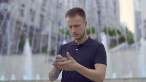 Knappe mens met speelkaarten bij fonteinachtergrond stock videobeelden