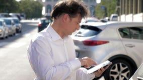 Knappe mens met wit overhemd die op de telefoon spreken die met tablet lopen stock videobeelden