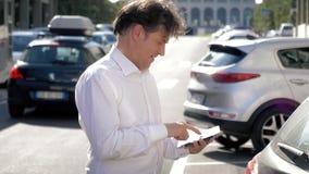 Knappe mens met wit overhemd die op de telefoon spreken die met tablet lopen stock video