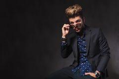 Knappe mens op donkere studioachtergrond die zijn zonnebril van start gaan Royalty-vrije Stock Foto