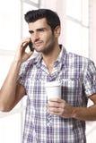 Knappe mens op telefoon met ochtendkoffie Royalty-vrije Stock Foto