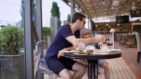 Knappe mens in toevallig blauw overhemd en kulassen die in restaurant met zoon en mensen op de achtergrond zitten Jonge vader stock videobeelden