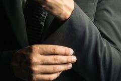 Knappe mens in zwart kostuum op een zwarte achtergrond Royalty-vrije Stock Foto's