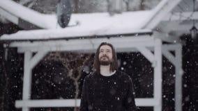Knappe mens in zwarte sweater die zich voor een oud blokhuis onder dalende sneeuw bevinden stock footage